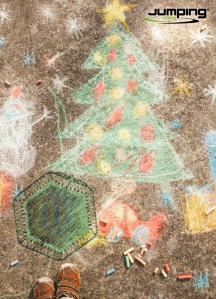 Boy drawing Christmas tree and decorations on the street.